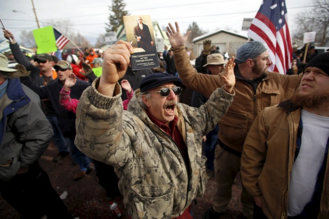 A pro-militia supporter holds a constitution while chanting